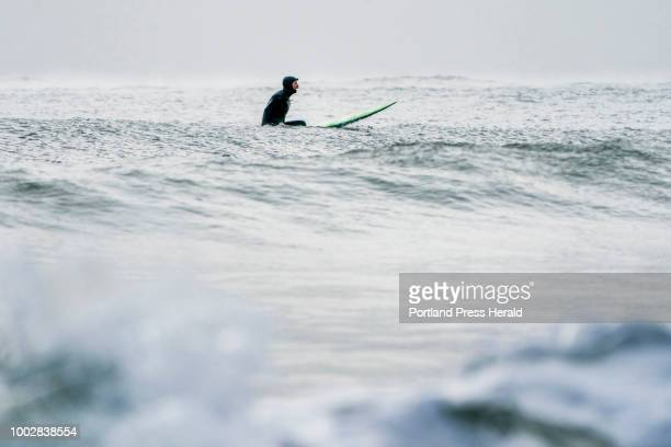 Don Parsons of Ogunquit bobs in the water as he waits for a wave while surfing in singledigit temperatures with belowzero windchills at Long Sands...