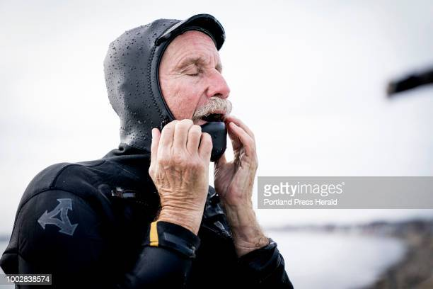 Don Parsons of Ogunquit struggles to remove his suit as his hands go numb in the singledigit temperatures with belowzero windchills at Long Sands...