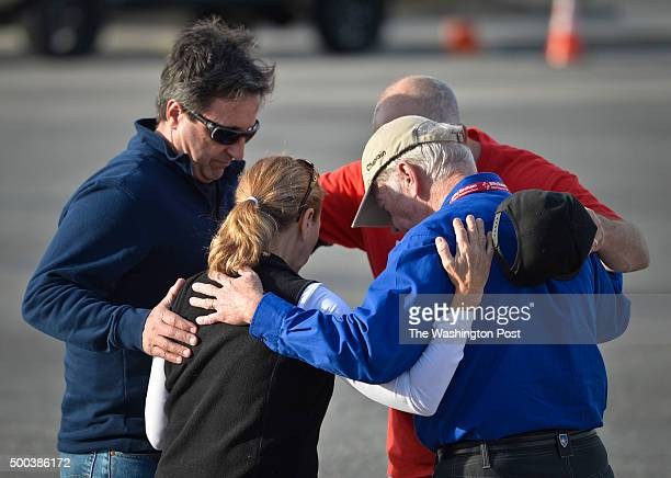 Don Puerling left Pam Puerling center and Chaplain Joe Henkes right pray Saturday afternoon at the site of a makeshift memorial for victims of...