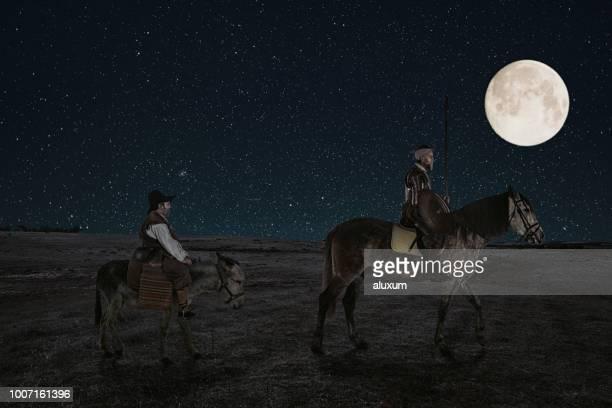 don quijote y sancho panza montando a través de campos por la noche en la mancha españa - don quijote de la mancha fotografías e imágenes de stock