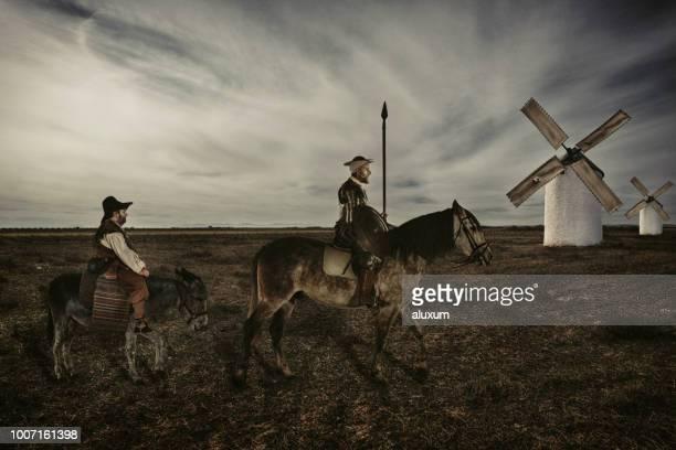 don quijote y sancho panza montando a través de campos de la mancha españa - don quijote de la mancha fotografías e imágenes de stock