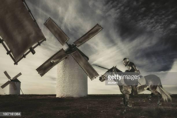 don quijote carga con su caballo contra molinos de viento la proyección de imagen son gigantes - don quijote de la mancha fotografías e imágenes de stock