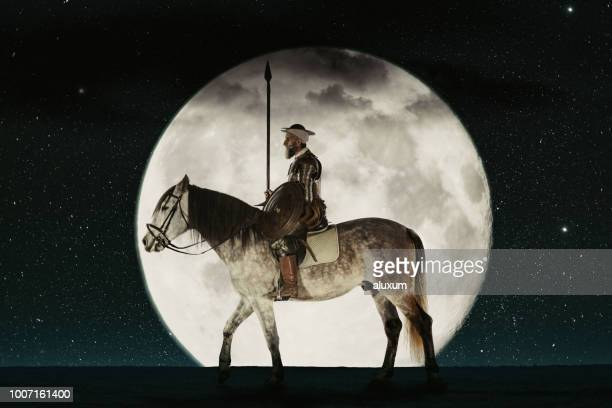 don quijote montado en su caballo contra la luna llena - castilla la mancha fotografías e imágenes de stock