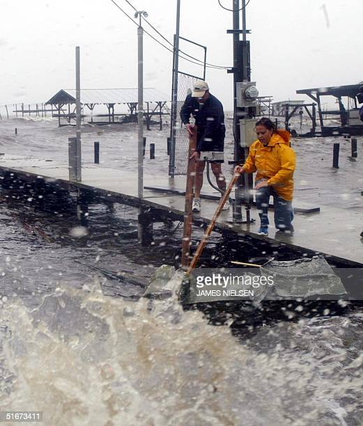 Don Schneider and Colette Cure push a small boat away from Cure's dock on Lake Pontchartrain that leads to her family's house in the Little Woods...