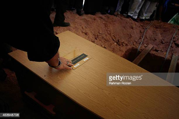 Don the brother of Dora Sheila Kassim touches her coffin before she is laid to rest at Bukit Kiara cemetery on August 22 2014 in Kuala Lumpur...