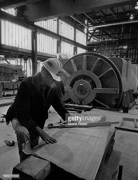 DEC 4 1969 DEC 9 1969 Don Warembourg Public Service Co resident engineer in charge of the Fort St Vrain job checks plans inside generator room...