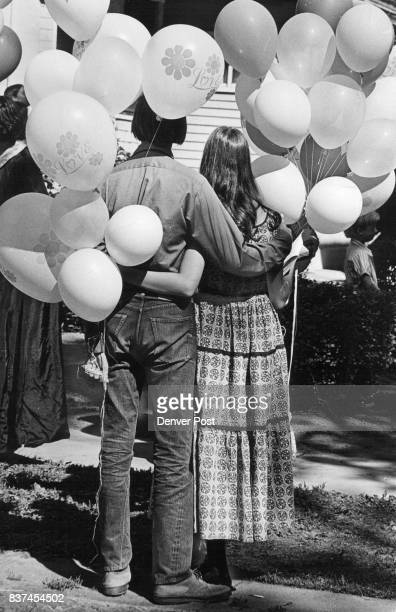 Don Westervelt of New Mexico and Karen Philips of Denver watch festivities as they grip strings of balloons Many participants dressed in attire...