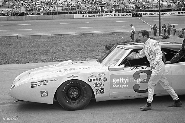 Don White pushes his Dodge Charger to the grid for the USAC stock car race as part of the unusual Twin Bill for stock and open wheel racers on July 4...