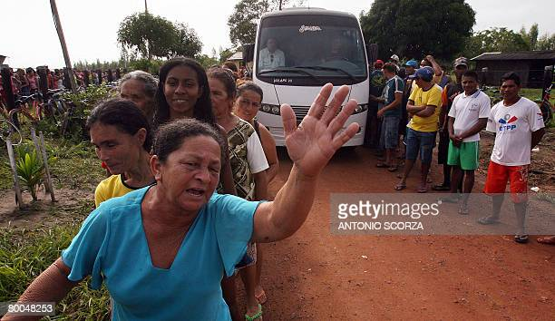 Dona Dina a resident of Tailandia in the northern Brazilian state of Para waves her arm to receive a basket of basic food at the entrance of the farm...