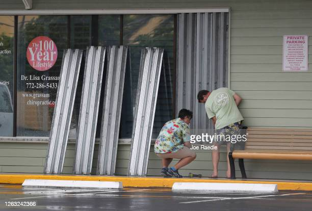 Donald Bowen and Doug Smith put shutters over the windows of their business as Tropical Storm Isaias approaches on August 01, 2020 in Stuart,...