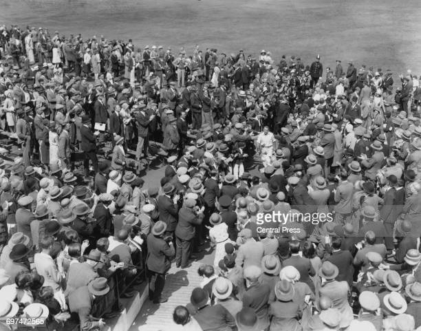 Donald Bradman of Australia returns to the pavillion amidst the congratulations of the spectators in the grandstand after his record scoring of 334...