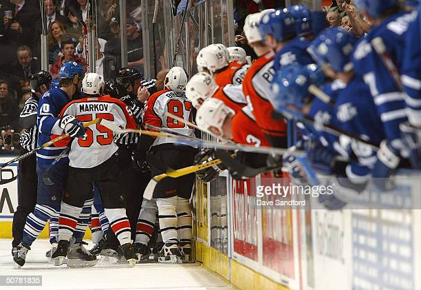 Donald Brashear and Danny Markov both of the Philadelphia Flyers mix it up with players from the Toronto Maple Leafs as both team benches look down...