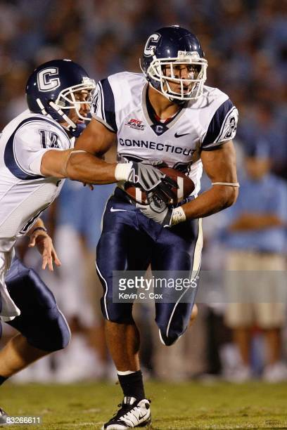 Donald Brown of the Connecticut Huskies takes the handoff from Zach Frazer during the game against the North Carolina Tar Heels at Kenan Stadium on...