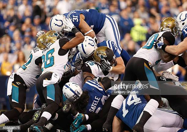 Donald Brown of the Indianapolis Colts dives over the pile of Jacksonville Jaguars defenders for a fist quarter touchdown at Lucas Oil Stadium on...