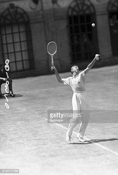 Donald Budge, star of the U.S. Davis Cup team, pictured in an excellent action pose, as he gave a powerful serve during his first match with Jack...