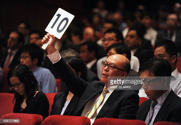 Donald Choi managing director of Nan Fung Development raises his paddle during a property auction in Hong Kong on July 28 2010 The Hong Kong...