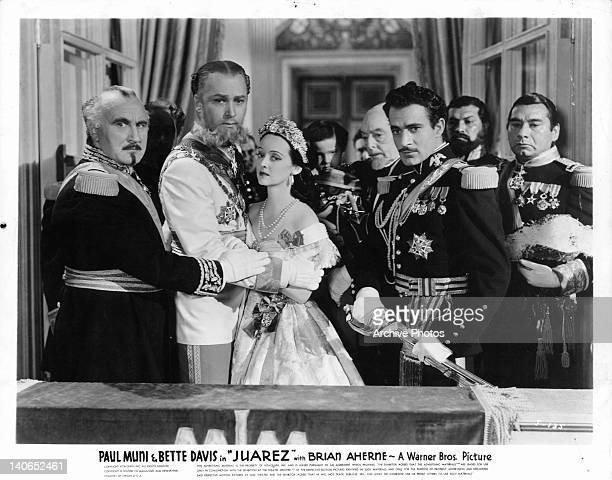Donald Crisp, Brian Aherne, Bette Davis, Harry Davenport, and Gilbert Roland looking down from balcony in a scene from the film 'Juarez', 1939.