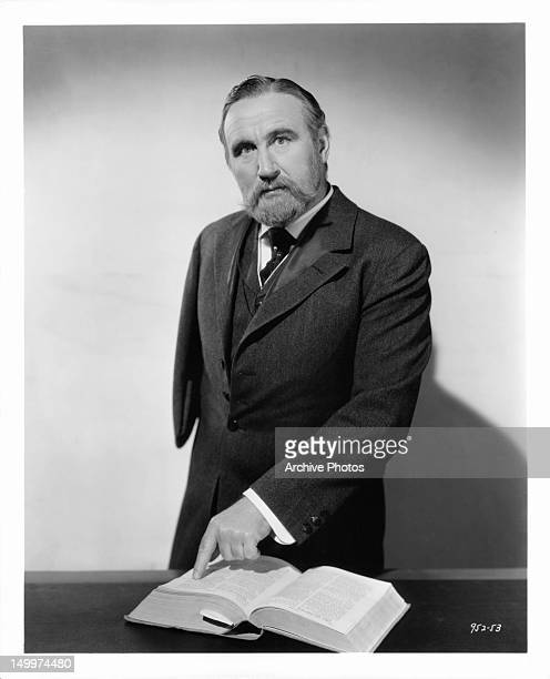 Donald Crisp pointing to thick book in publicity portrait for the film 'Parnell', 1937.
