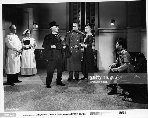 Donald Crisp stands proud in front of crowd as a sitting Tyrone Power watches in a scene from the film 'The Long Gray Line', 1955.
