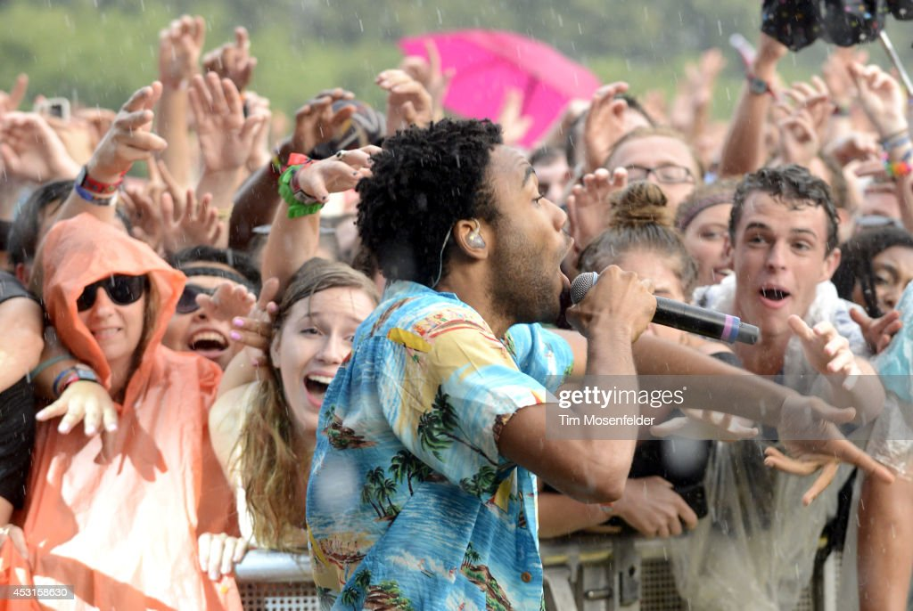 Donald Glover of Childish Gambino performs in the rain during 2014 Lollapalooza at Grant Park on August 3, 2014 in Chicago, Illinois.