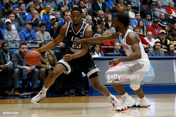 Donald Hicks of the Radford Highlanders defends against Raiquan Clark of the LIU Brooklyn Blackbirds during the game at UD Arena on March 13 2018 in...