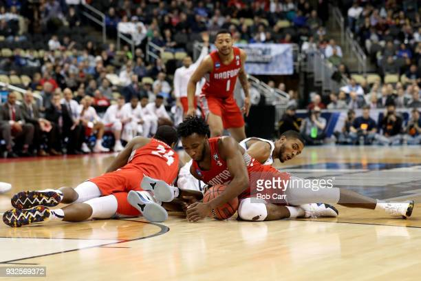 Donald Hicks of the Radford Highlanders fights for the ball on the ground against Mikal Bridges of the Villanova Wildcats during the first half of...