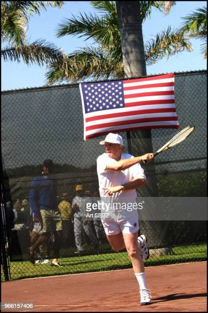 Donald J Trump blasting a forehand winner from the baselinewith a red white and blue flag directly over his head