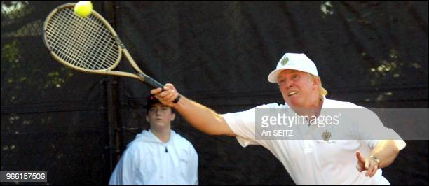 Donald J Trump wearing a hat and shirt with a large MaraLago crest/logo stretching with his gold colored Prince Tennis Racquet for a high forehand