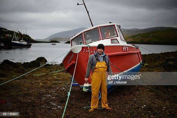 Donald John Macleod paints a fishing boat in Scalpay on May 15 2014 in Harris Scotland The Isles of Lewis and Harris lie in the Outer Hebrides and...