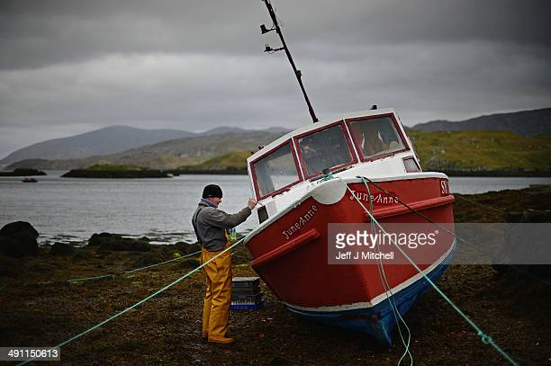 Donald John Macleod paints a fishing boat in Scalpay on May 15, 2014 in Harris, Scotland. The Isles of Lewis and Harris lie in the Outer Hebrides and...