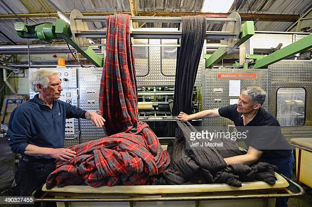 Donald Mackay Iain Macdonald work in the finishing department at the Harris Tweed Hebrides Company in Shawbost on May 13 2014 in Stornoway Scotland...