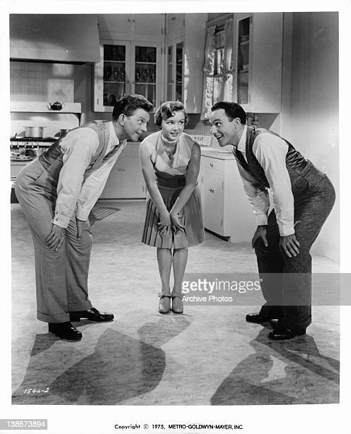 Donald O'Connor Debbie Reynolds and Gene Kelly hunching over together in a scene from the film 'Singin' In The Rain' 1952