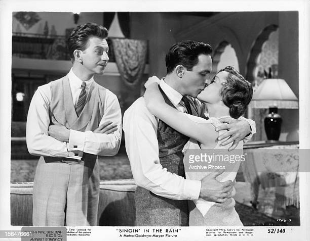 Donald O'Connor watches as Gene Kelly kisses Debbie Reynolds in a scene from the film 'Singin' In The Rain' 1952