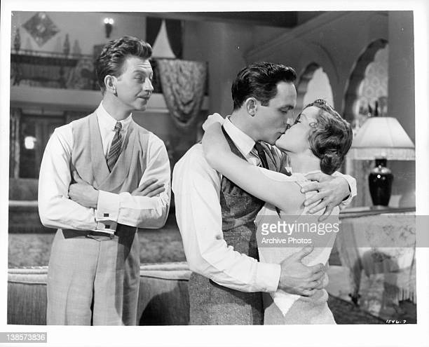 Donald O'Connor watching Gene Kelly and Debbie Reynolds kiss in a scene from the film 'Singin' In The Rain' 1952