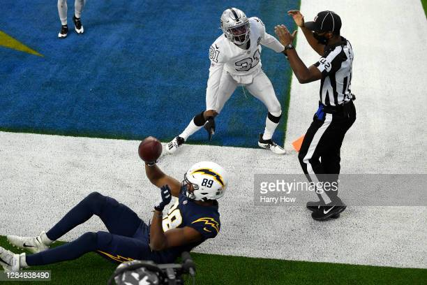 Donald Parham of the Los Angeles Chargers celebrates a fourth quarter touchdown catch while Isaiah Johnson of the Las Vegas Raiders objects at SoFi...