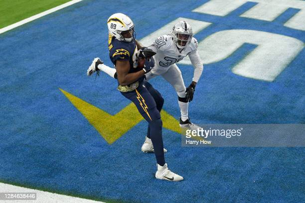 Donald Parham of the Los Angeles Chargers tries to come down with a fourth quarter touchdown catch next to Isaiah Johnson of the Las Vegas Raiders at...