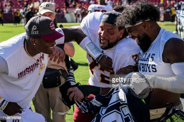 Donald Penn of the Washington Redskins laughs with Dwayne Haskins and Ezekiel Elliott of the Dallas Cowboys R| after the game at FedExField on...