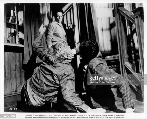 Donald Sutherland and Maurice Kaufmann fight while Yootha Joyce watches in a scene from the film 'Die Die My Darling' 1965