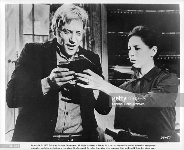 Donald Sutherland is excited to read book that Yootha Joyce is holding for him in a scene from the film 'Die Die My Darling' 1965
