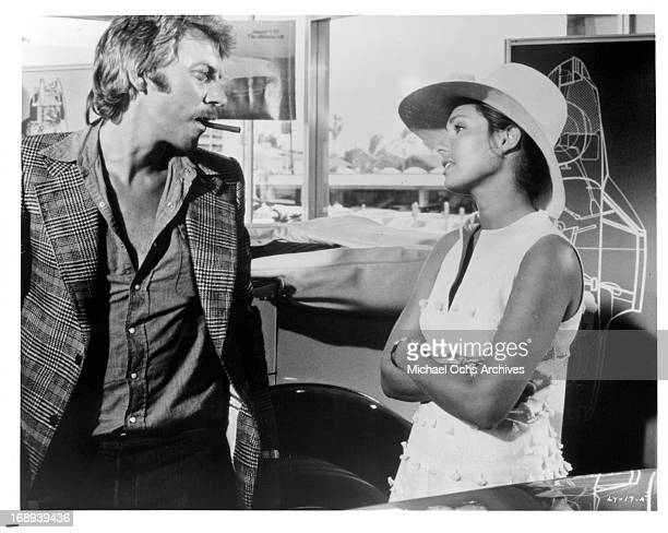 Donald Sutherland tries to sell a necklace to Jennifer O'Neill in a scene from the film 'Lady Ice' 1973