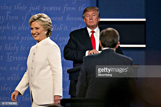 Donald Trump 2016 Republican presidential candidate stands as Hillary Clinton 2016 Democratic presidential candidate exits the stage after the third...