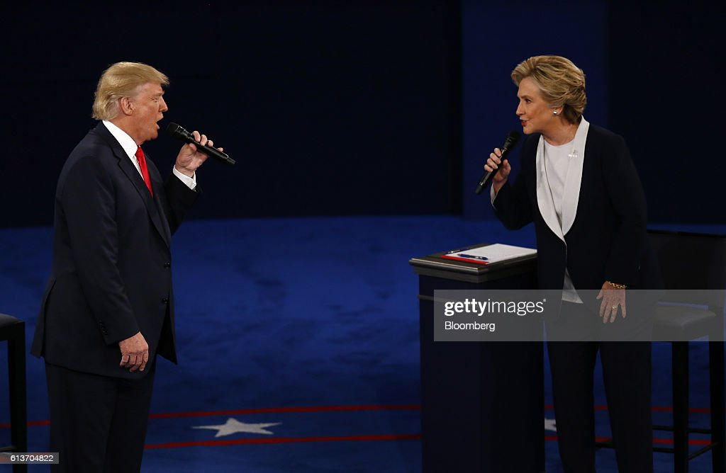 Donald Trump, 2016 Republican presidential nominee, and Hillary Clinton, 2016 Democratic presidential nominee, speak during the second U.S. presidential debate at Washington University in St. Louis, Missouri, U.S., on Sunday, Oct. 9, 2016. As has become tradition, the second debate will resemble a town hall meeting, with the candidates free to sit or roam the stage instead of standing behind podiums, while members of the audience -- uncommitted voters, screened by the Gallup Organization -- will ask half the questions. Photographer: Andrew Harrer/Bloomberg via Getty Images