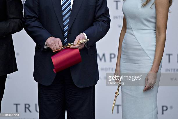 Donald Trump 2016 Republican presidential nominee left and his wife Melania Trump hold scissors after cutting a ribbon during the grand opening...