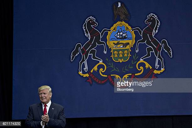 Donald Trump 2016 Republican presidential nominee stands in front of the Pennsylvania state flag as he arrives to speak during a campaign rally in...