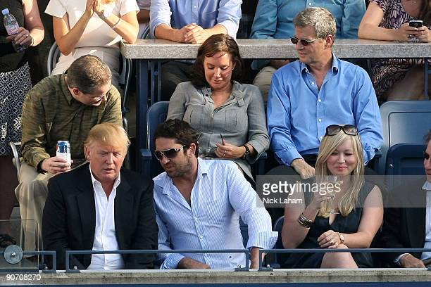 Donald Trump and actor Gerard Butler watch the match between Roger Federer of Switzerland and Novak Djokovic of Serbia during day fourteen of the...