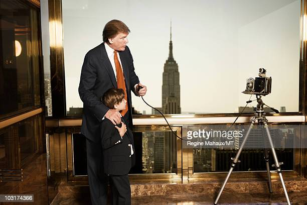 Donald Trump and Barron Trump pose for a portrait on April 14 2010 in New York City Donald Trump is wearing a suit and tie by Brioni Barron Trump is...