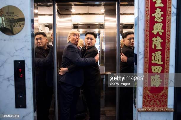 Donald Trump and Kim Jongun impersonators jokingly hug each other in a elevator