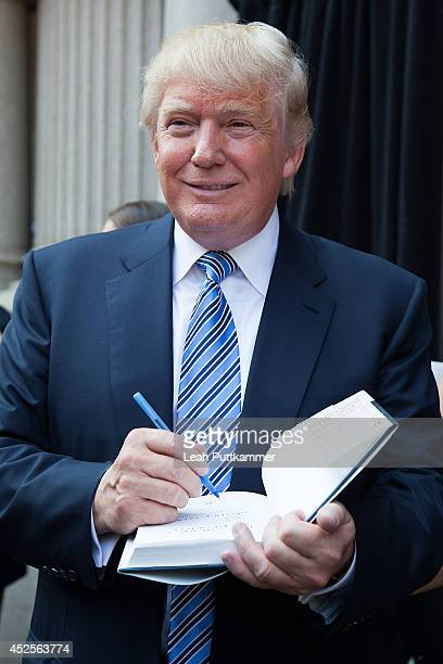 Donald Trump autographs book at the Trump International Hotel Washington, D.C Groundbreaking Ceremony on July 23, 2014 in Washington, DC.