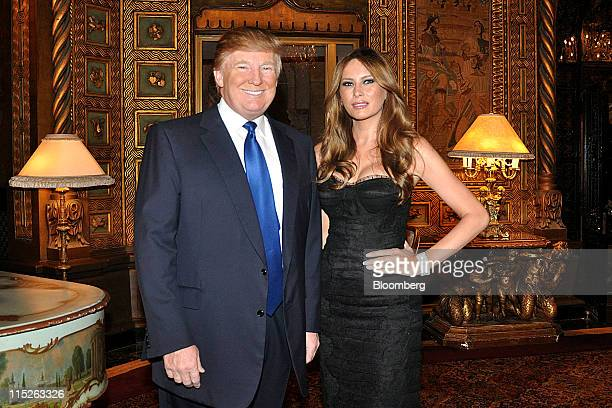 Donald Trump billionaire real estate developer left and his wife Melania Trump stand for a photograph at the MarALago Club in Palm Beach Florida US...