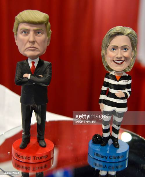 A Donald Trump bobblehead doll is displayed beside one of former US ecretary of State Hillary Clinton in prison garb at a booth during the...